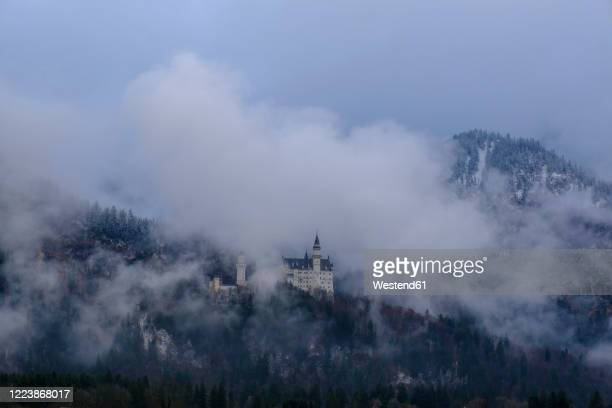 germany, bavaria, hohenschwangau, aerial view ofneuschwanstein castleshrouded in fog - local landmark stock pictures, royalty-free photos & images