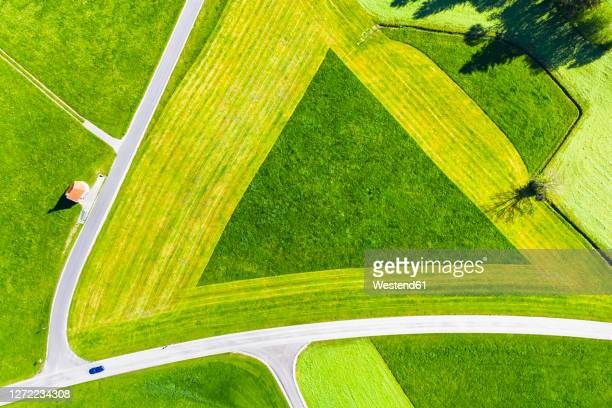 germany, bavaria, hopferau, drone view of kapelle saint antonius and triangle shaped field in spring - triangle shape stock pictures, royalty-free photos & images
