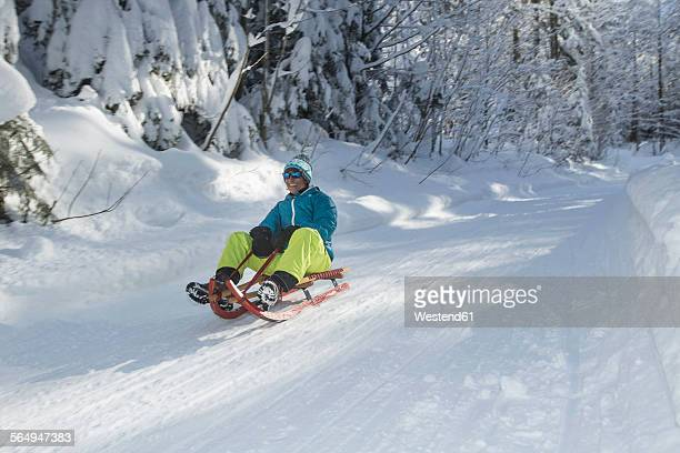 Germany, Bavaria, Inzell, man having fun on a sledge in snow-covered landscape