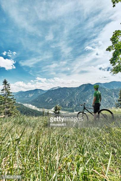 germany, bavaria, isar valley, karwendel mountains, mountainbiker on a trip having a break on alpine meadow - karwendel mountains stock pictures, royalty-free photos & images