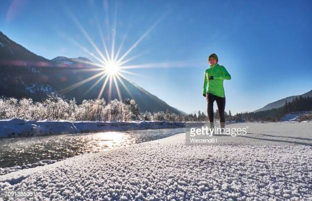 germany, bavaria, isar valley, vorderriss, woman jogging in winter - fiume isar foto e immagini stock