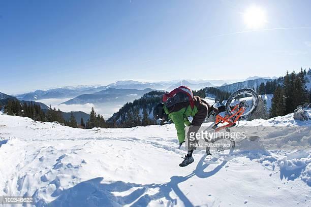 Germany, Bavaria, Kampenwand, Mountain biker falling off bike in snow