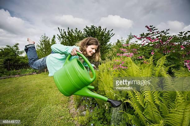 Germany, Bavaria, Kaufbeuren, Mid adult woman watering plants in garden