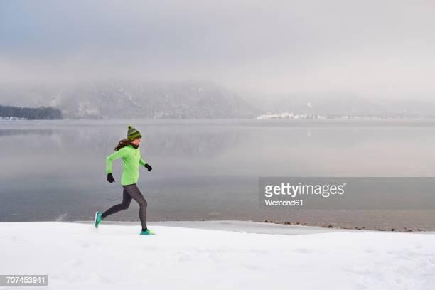 Germany, Bavaria, Lake Kochel, woman jogging in winter