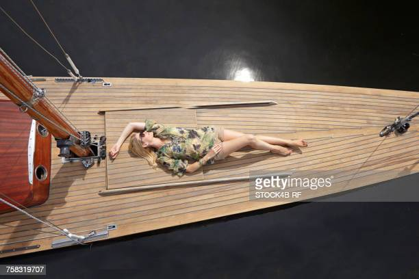"""""""germany, bavaria, lake starnberg, woman lying on deck of a sailboat"""" - starnberg photos et images de collection"""
