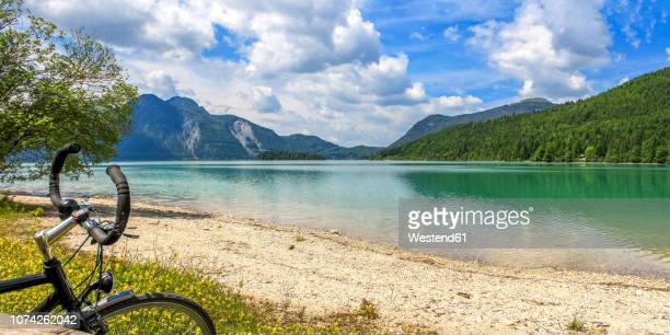 germany, bavaria, lake walchen, bicycle in the foreground - küste stock-fotos und bilder