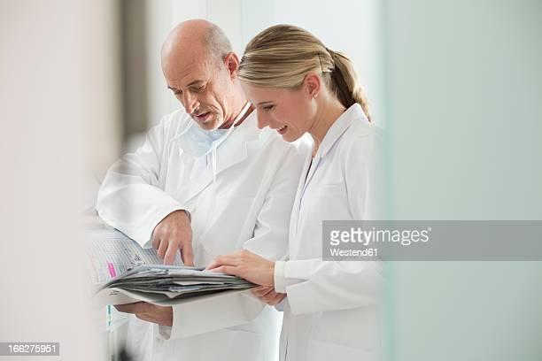 Germany, Bavaria, Landsberg, Dentist and assistant holding documents