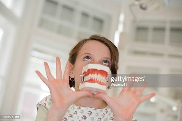 germany, bavaria, landsberg, girl (8-9) holding model of teeth, portrait - dentist horror stockfoto's en -beelden
