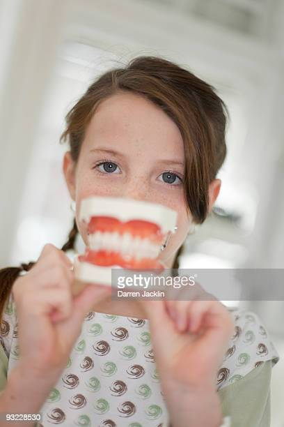 Germany, Bavaria, Landsberg, Girl (8-9) holding model of teeth, portrait