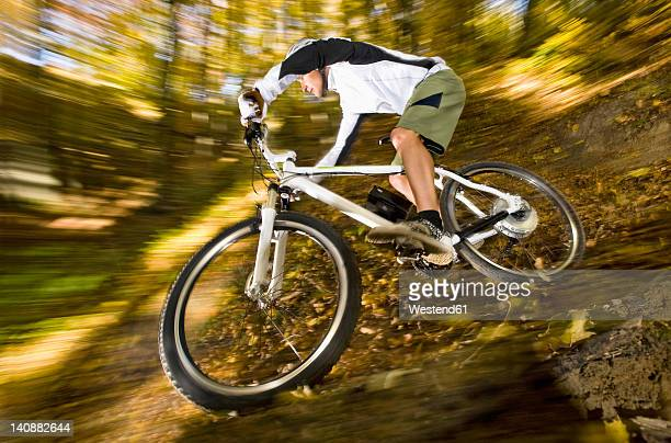 Germany, Bavaria, Landshut, Man riding electric mountain bike in forest