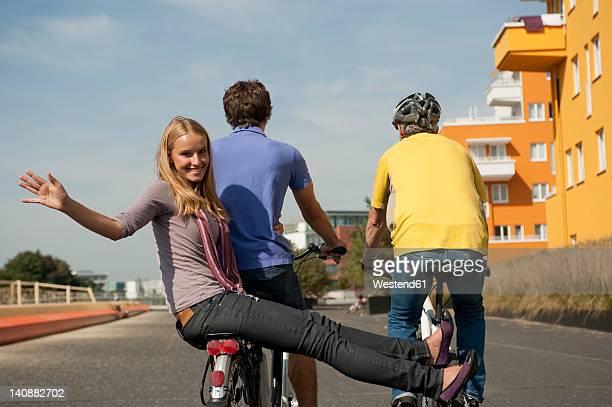 Germany, Bavaria, Man riding bicycle and girl sitting back, smiling