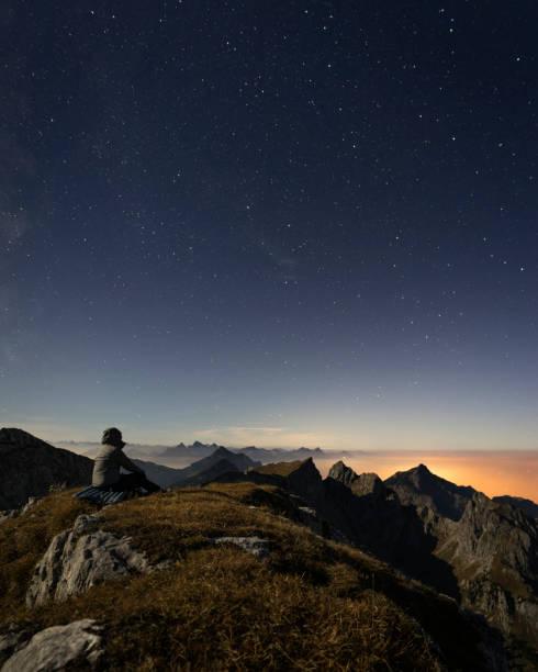Germany, Bavaria, Man sitting at summit of Ammergau Hochplatte mountain at dusk