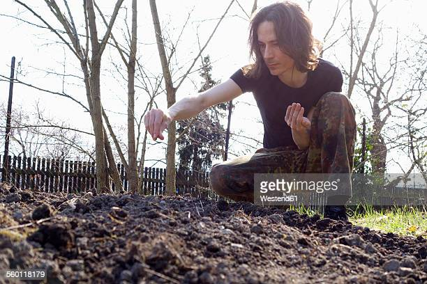 Germany, Bavaria, Man sowing in organic garden