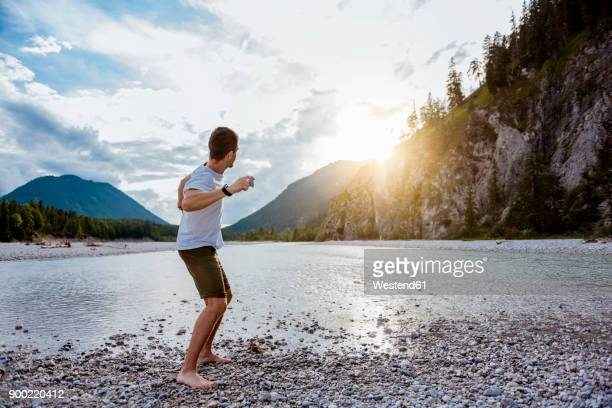 germany, bavaria, man standing at riverside throwing stone - throwing stock pictures, royalty-free photos & images