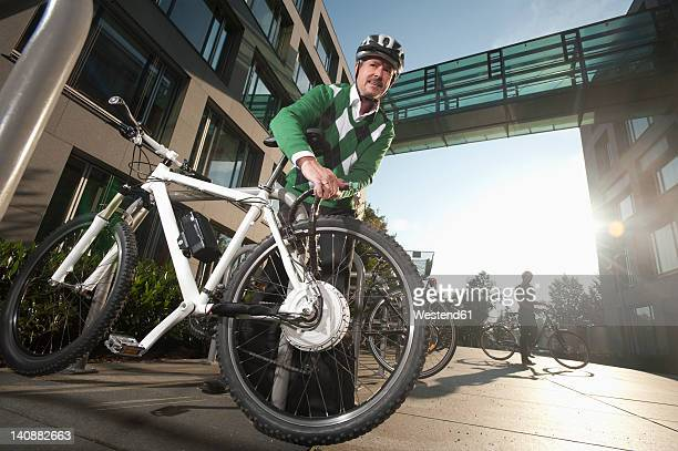 Germany, Bavaria, Mature man fixing lock of bicycle
