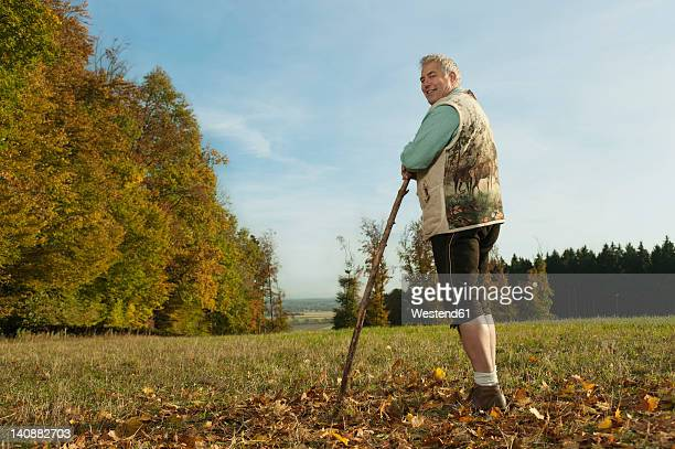 Germany, Bavaria, Mature man in traditional vest with cane, smiling, portrait