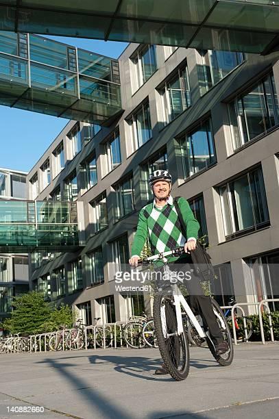 Germany, Bavaria, Mature man on bicycle, smiling, portrait