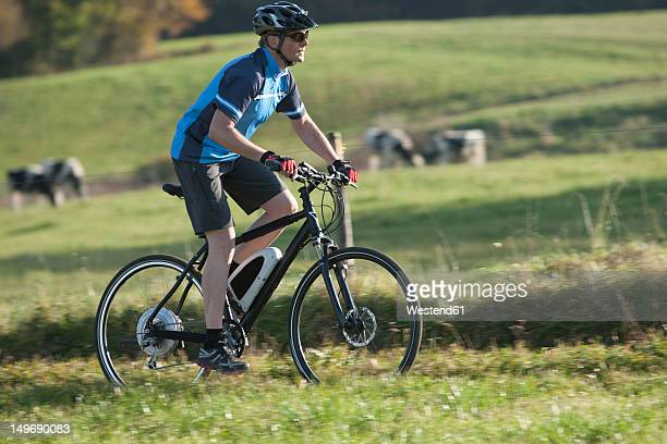Germany, Bavaria, Mature man riding electric bicycle
