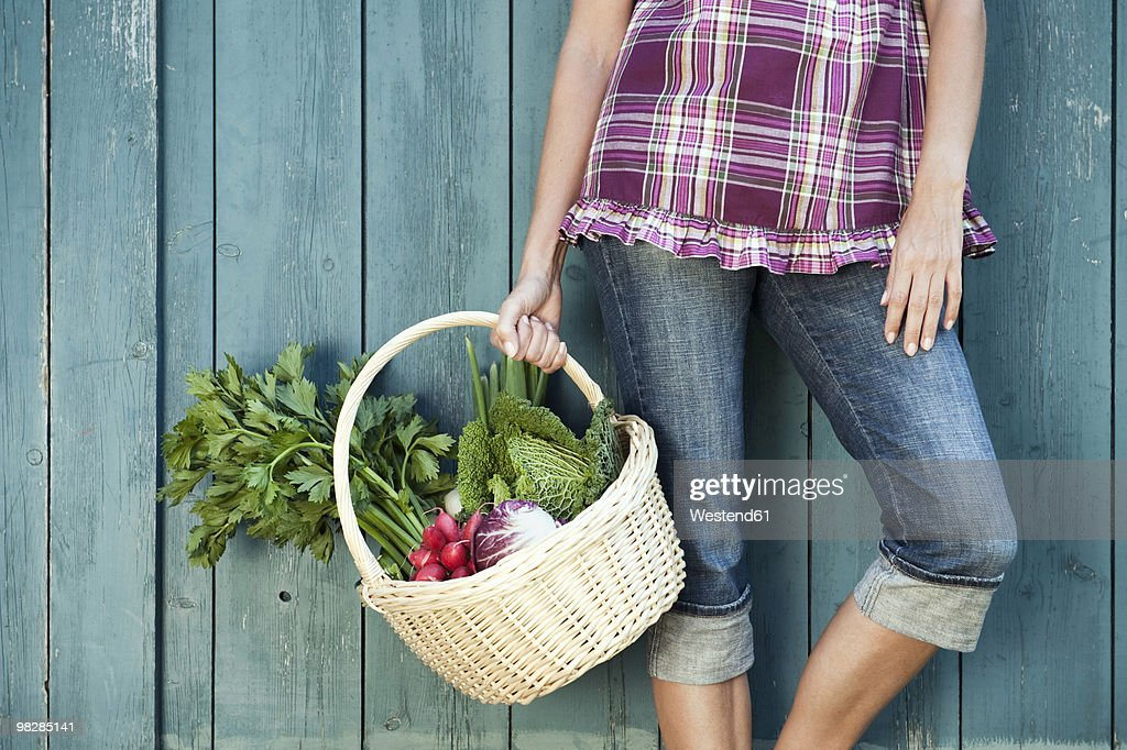 Germany, Bavaria, Mature woman holding vegetable basket : Stock Photo