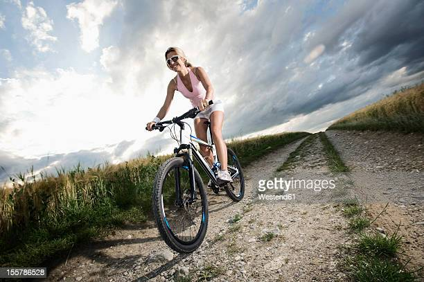Germany, Bavaria, Mature woman riding mountain bike in grain field