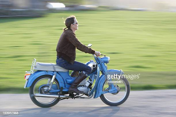 germany, bavaria, mature woman riding old moped of 1960s - moped stock photos and pictures