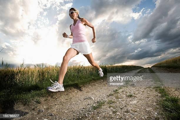 germany, bavaria, mature woman running in grain field - aktiver lebensstil stock-fotos und bilder