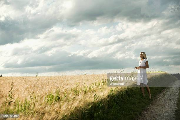 germany, bavaria, mature woman standing in grain field - focus on background stock pictures, royalty-free photos & images