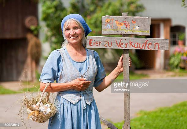 Germany, Bavaria, Mature woman standing next to sign board