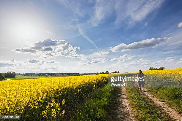 Germany, Bavaria, Mature woman walking through oilseed rape
