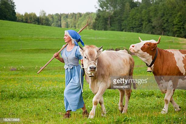 Germany, Bavaria, Mature woman with cow on farm