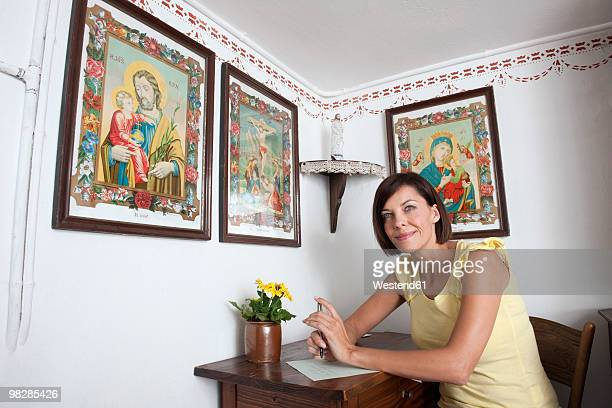 Germany, Bavaria, Mature woman writing letter, smiling