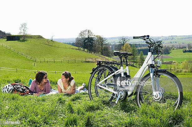 Germany, Bavaria, Mature women lying on grass, electric bicycle in foreground