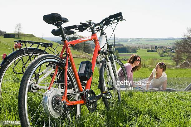Germany, Bavaria, Mature women sitting on grass, electric bicycle in foreground