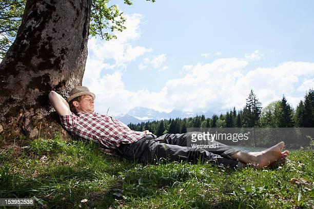 Germany, Bavaria, Mid adult man lying on grass under tree