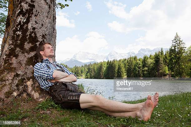 Germany, Bavaria, Mid adult man relaxing under tree