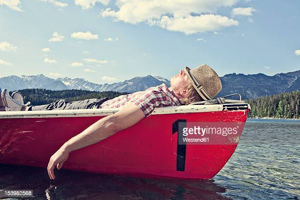 germany, bavaria, mid adult man sleeping in rowing boat - männer über 30 stock-fotos und bilder