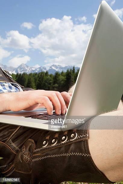 germany, bavaria, mid adult man using laptop - レーダーホーゼン ストックフォトと画像