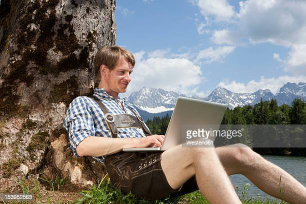 Germany, Bavaria, Mid adult man using laptop under tree