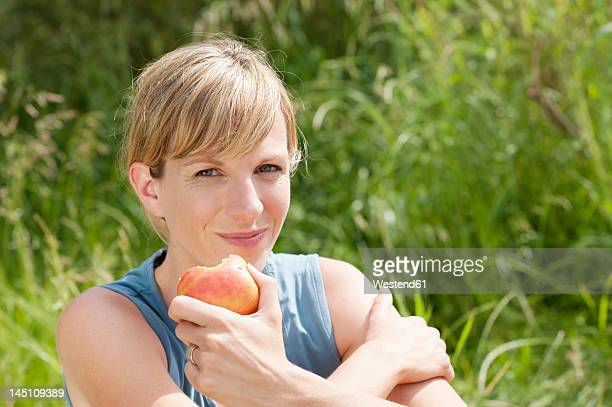 Germany, Bavaria, Mid adult woman eating apple, smiling, portrait