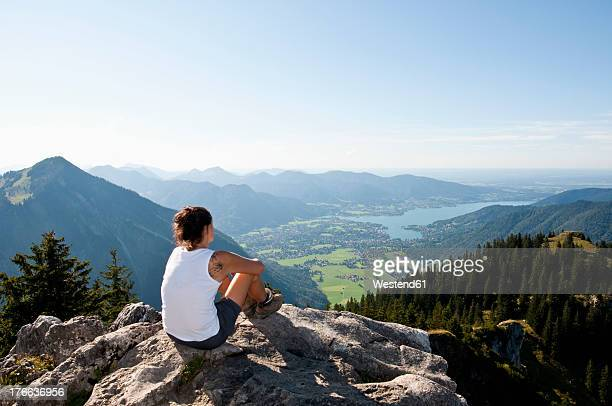 Germany, Bavaria, Mid adult woman looking from Bodenschneid to lake Tegernsee