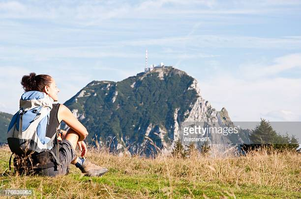 Germany, Bavaria, Mid adult woman sitting in meadow and looks to Wendelstein