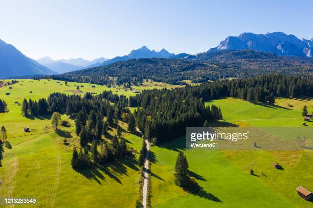 germany, bavaria, mittenwald, drone view of buckelwiesen meadow in spring with wetterstein mountains in background - mittenwald stock pictures, royalty-free photos & images
