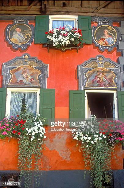 Germany Bavaria Mittenwald Europe Luftmaileri painted facade detail of local building with flowers and window boxes.
