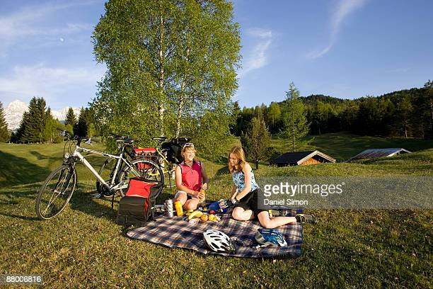 germany, bavaria, mittenwald, two women with mountain bikes having a picnic - mittenwald stock pictures, royalty-free photos & images