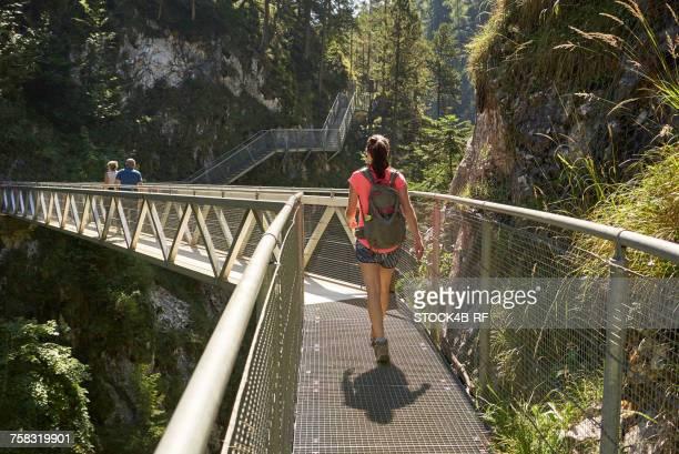 """germany, bavaria, mittenwald, woman on footbridge in leutasch gorge"" - mittenwald fotografías e imágenes de stock"