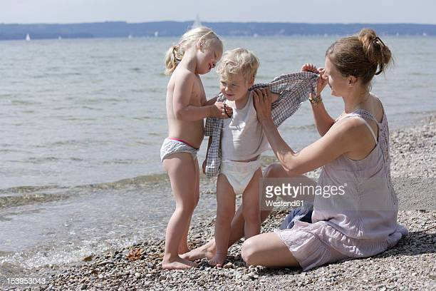 germany, bavaria, mother and daughter helping son to undress - little girl taking off clothes stock photos and pictures