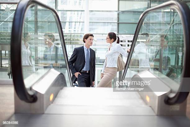 Germany, Bavaria, Munich, Businesspeople standing on escalator in airport