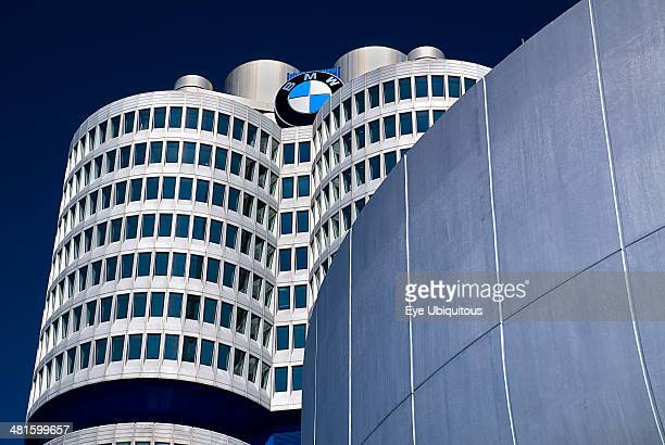 Germany Bavaria Munich BMW Headquarters exterior BMW Tower which stands 101 meters tall and mimics the shape of tires part view seen behind curved...