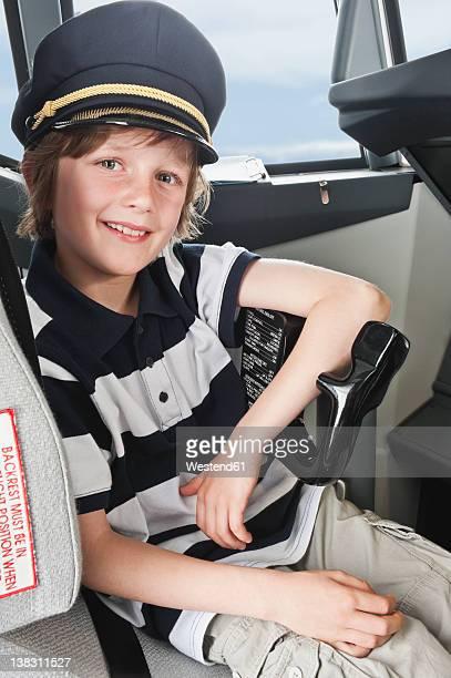 germany, bavaria, munich, boy wearing captain's hat and playing in airplane cockpit - uniform cap imagens e fotografias de stock