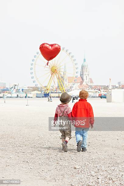 Germany, Bavaria, Munich, boys with heart shaped balloon going to Oktoberfest